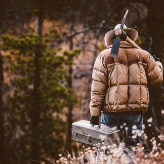 Working Outdoorsman Carries Tools While Heading Down Wooded Hill